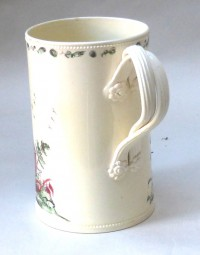 Creamware mug decorated with two ladies in a landscape